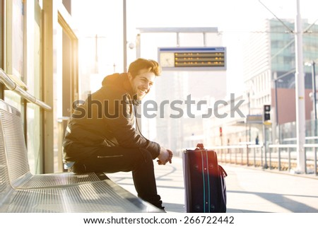 Portrait of a happy young man waiting for train at station with bag - stock photo
