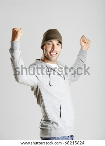 Portrait of a happy young man with arms on the air - stock photo