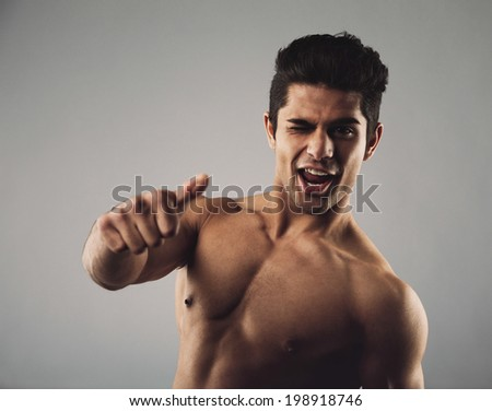 Portrait of a happy young man with muscular physique winking and giving a thumbs up sign. Shirtless young hispanic man on grey background. Focus on hand. - stock photo