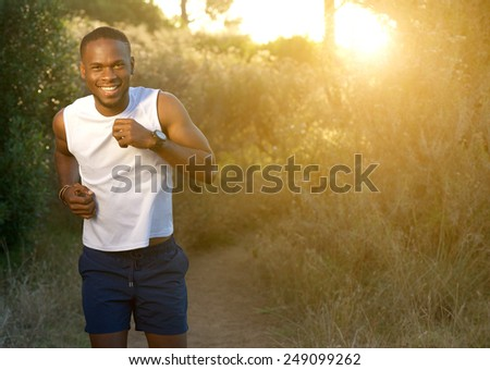 Portrait of a happy young sports man running outdoors  - stock photo