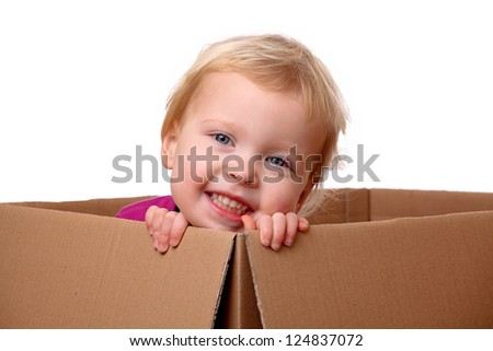 Portrait of a happy young toddler sitting in a box - stock photo