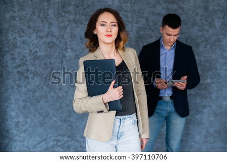 Portrait of a happy young woman holding laptop and looking at camera.  - stock photo