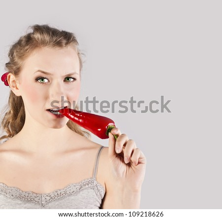 Portrait of a happy, young woman, holding red hot chilli