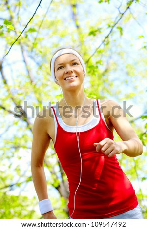Portrait of a happy young woman jogging outside