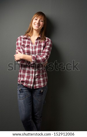 Portrait of a happy young woman on gray background - stock photo