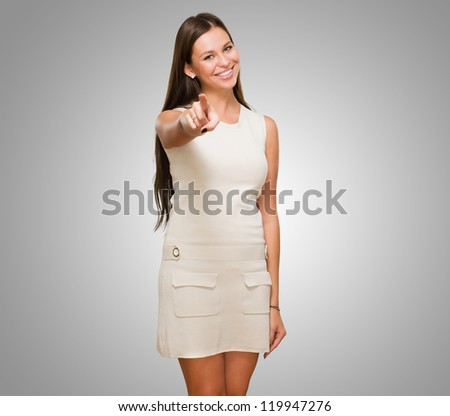 Portrait Of A Happy Young Woman Pointing At You against a grey background - stock photo