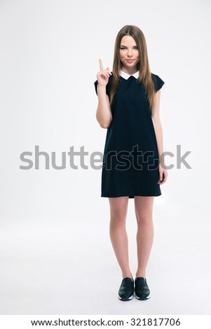 Portrait of a happy young woman pointing finger up at copyspace isolated on a white background. Looking at camera - stock photo