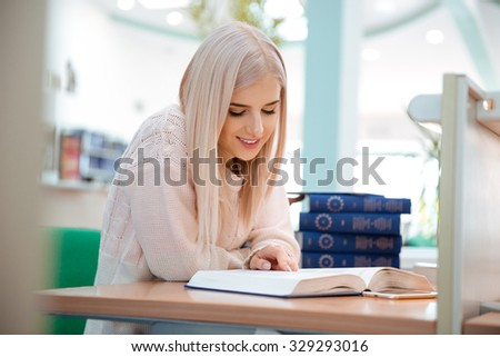 Portrait of a happy young woman reading book in university - stock photo