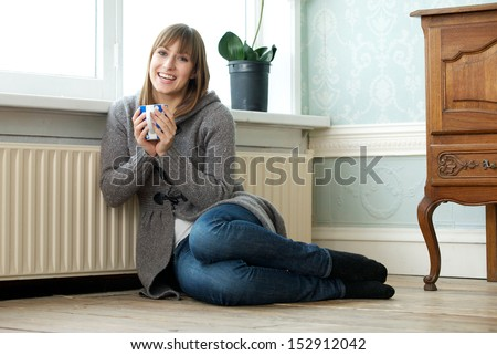 Portrait of a happy young woman relaxing at home with a cup of tea - stock photo
