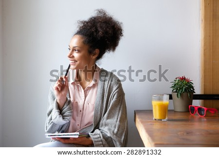 Portrait of a happy young woman sitting at home with pen and paper - stock photo