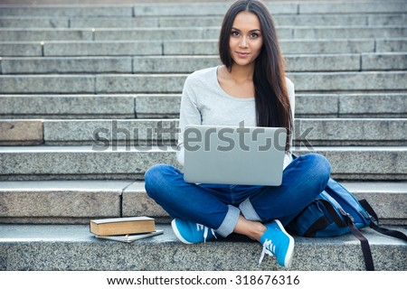 Portrait of a happy young woman sitting on the city stairs and using laptop computer outdoors - stock photo