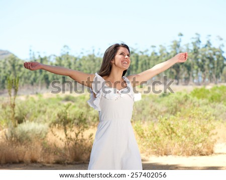Portrait of a happy young woman smiling with arms spread open - stock photo