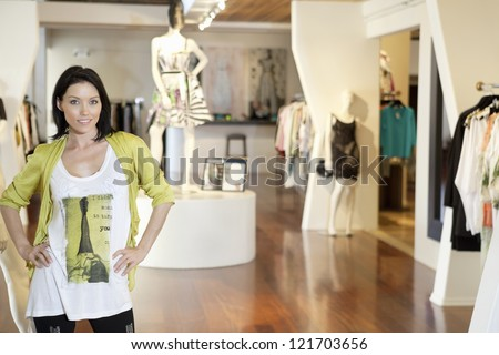 Portrait of a happy young woman standing with hands on hips in fashion clothing store - stock photo