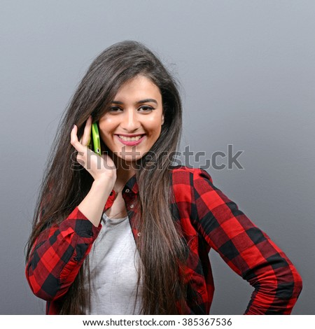 Portrait of a happy young woman talking on a cellphone against gray background - stock photo