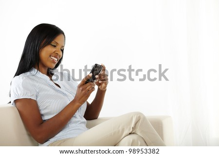 Portrait of a happy young woman using mobile phone - stock photo