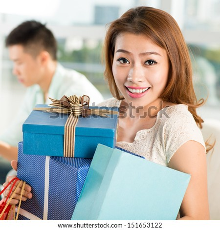Portrait of a happy young woman with lots of presents on the foreground - stock photo
