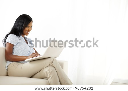 Portrait of a happy young woman working on laptop and having fun - stock photo