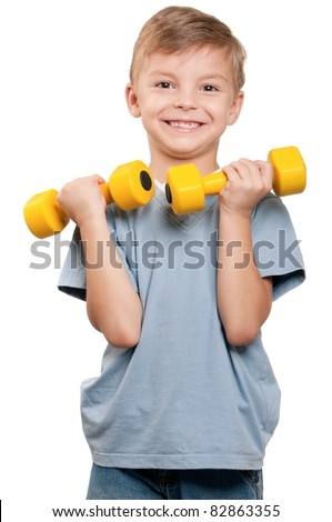 Portrait of a healthy little boy working out with dumbbells over white background