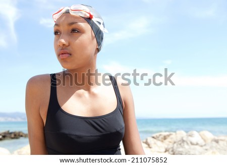 Portrait of a healthy sporty african american young woman swimmer sitting on a beach with goggles and a swimming cap, relaxing being thoughtful while training in nature. Sport lifestyle outdoors.
