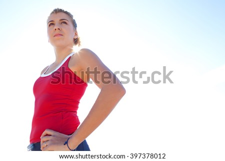 Portrait of a healthy sporty caucasian adolescent girl standing focused against the blue sky with sun flare filtering through, outdoors. Young woman training, wellness lifestyle and sport, exterior. - stock photo