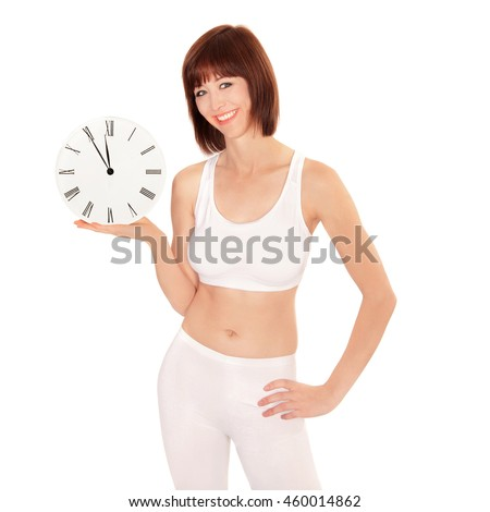 Portrait of a healthy young woman holding a clock showing five minutes to twelve, isolated on white studio background - stock photo