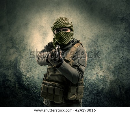 Portrait of a heavily armed masked soldier with grungy background concept - stock photo