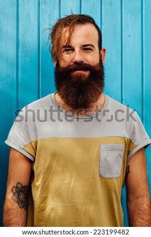 Portrait of a hipster style bearded man looking at the camera. - stock photo