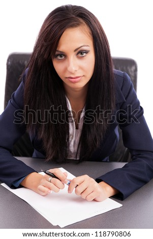 Portrait of a hispanic businesswoman writing while sitting at desk - stock photo
