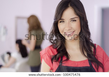 Portrait of a hispanic hairstylist in a beauty salon - stock photo