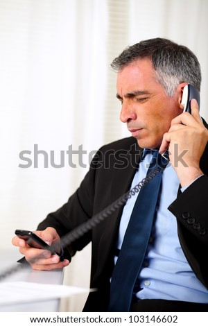 Portrait of a hispanic senior business man calling on phone at workplace - stock photo