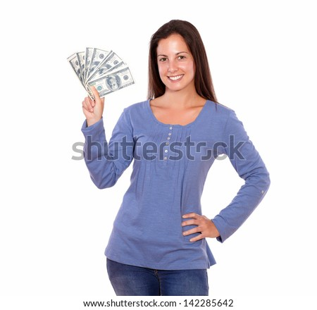 Portrait of a hispanic woman holding dollars while standing on white background