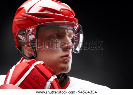 Portrait of a hockey player against black backround - stock photo