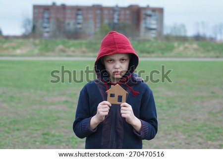 portrait of a homeless boy holding a cardboard house - stock photo