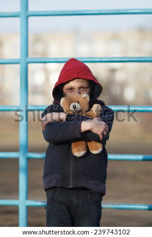 portrait of a homeless young boy with bear - stock photo
