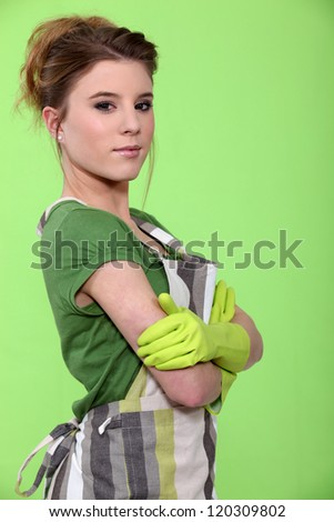 Portrait of a housewife wearing rubber gloves and an apron - stock photo