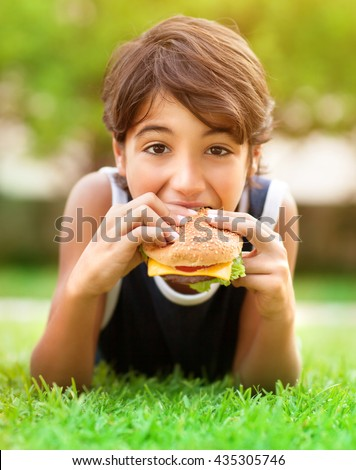 Portrait of a hungry teen boy lying down on fresh green grass and eating burger, enjoying picnic outdoors, summer holidays in the camp - stock photo