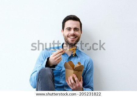 Portrait of a hungry young man smiling with chopsticks - stock photo
