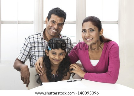 Portrait of a Indian family in kitchen relaxing together. - stock photo