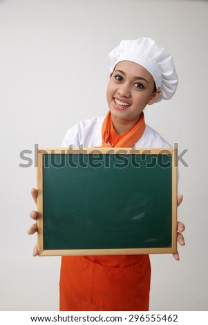 Portrait of a Indian woman with chef uniform holding chalk board - stock photo