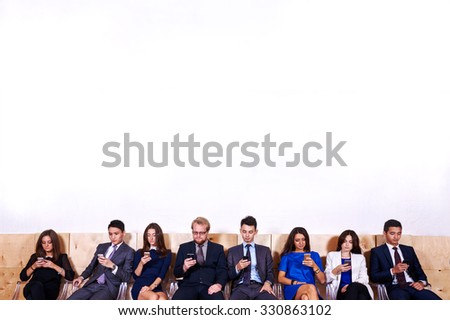 Portrait of a International group of a young skilled economists or business people using smart phones in waiting room against wall background with copy space for your text message or promotion content - stock photo