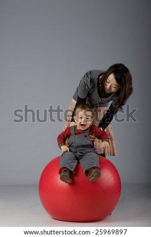 portrait of a japanese mother and toddler son playing on a fit pall - stock photo