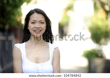 portrait of a japanese woman outdoors with copyspace and blur - stock photo