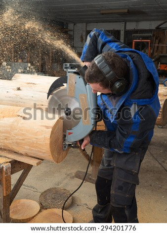 Portrait of a joiner sawing tree trunk with chainsaw in his workshop - stock photo