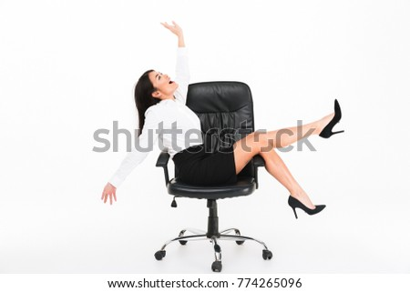 Portrait of a joyful asian businesswoman in eyeglasses having fun while sitting in an office chair isolated over white background