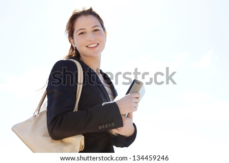 Portrait of a joyful businesswoman carrying work folders and smiling at the camera against a sunny blue sky.
