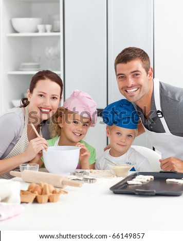 Portrait of a joyful family cooking cakes in the kitchen - stock photo