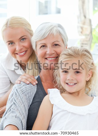 Portrait of a joyful family looking at the camera at home - stock photo
