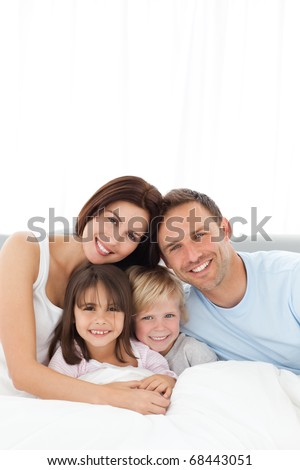 Portrait of a joyful family sitting on the bed at home - stock photo
