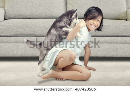 Portrait of a joyful little girl having fun with siberian husky puppy on the floor at home