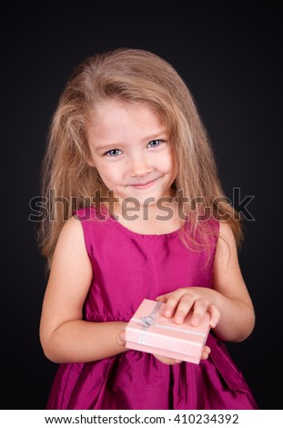 Portrait of a joyful little girl in a pink dress with a gift in her hands on a black background in the studio - stock photo
